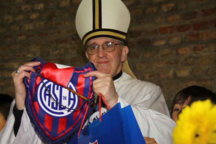 Cardinal Jorge Bergoglio holds up a small flag of the San Lorenzo soccer team in Buenos Aires, Argentina, March 24, 2011.