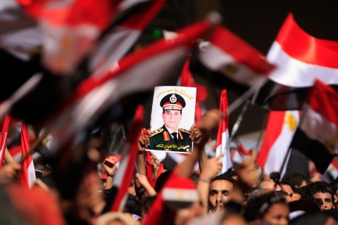 Protesters, who are against Egyptian President Mohamed Mursi, hold a poster featuring the head of Egypt's armed forces General Abdel Fattah al-Sisi, in Tahrir Square in Cairo